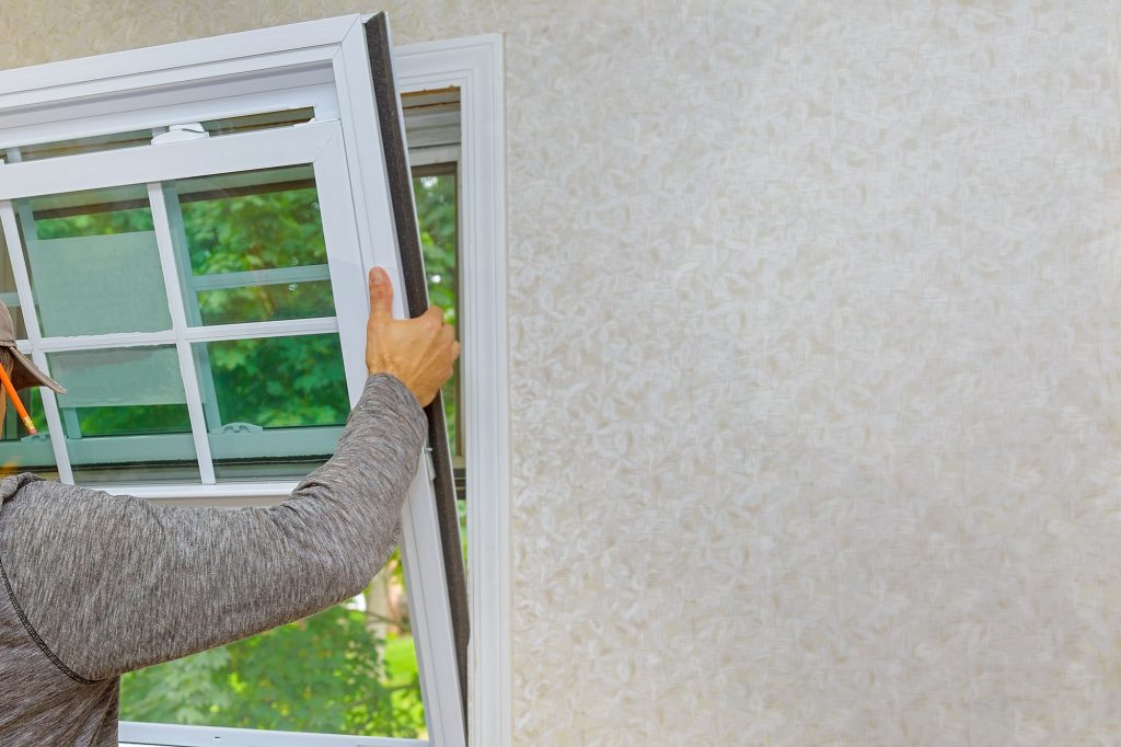 Worker in the installing new, windows in an house, with a new window in the home renovation living
